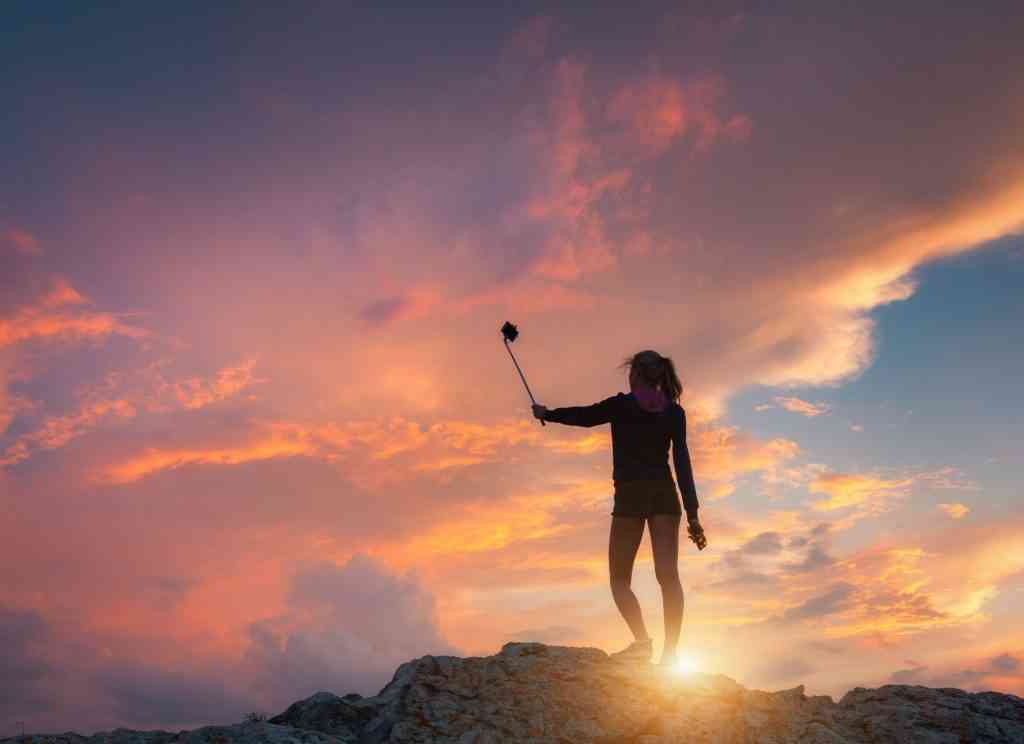 Beautiful young woman makes selfie for Instagram at sunset