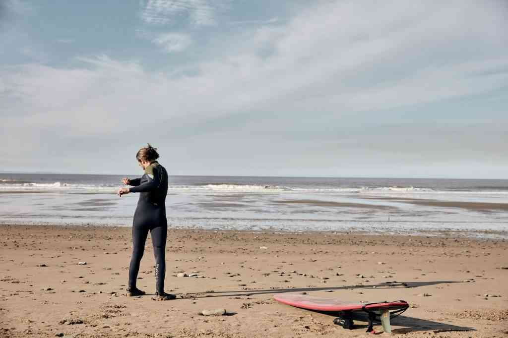 Man exercising, stretching and warming up on a sandy beach before surfing